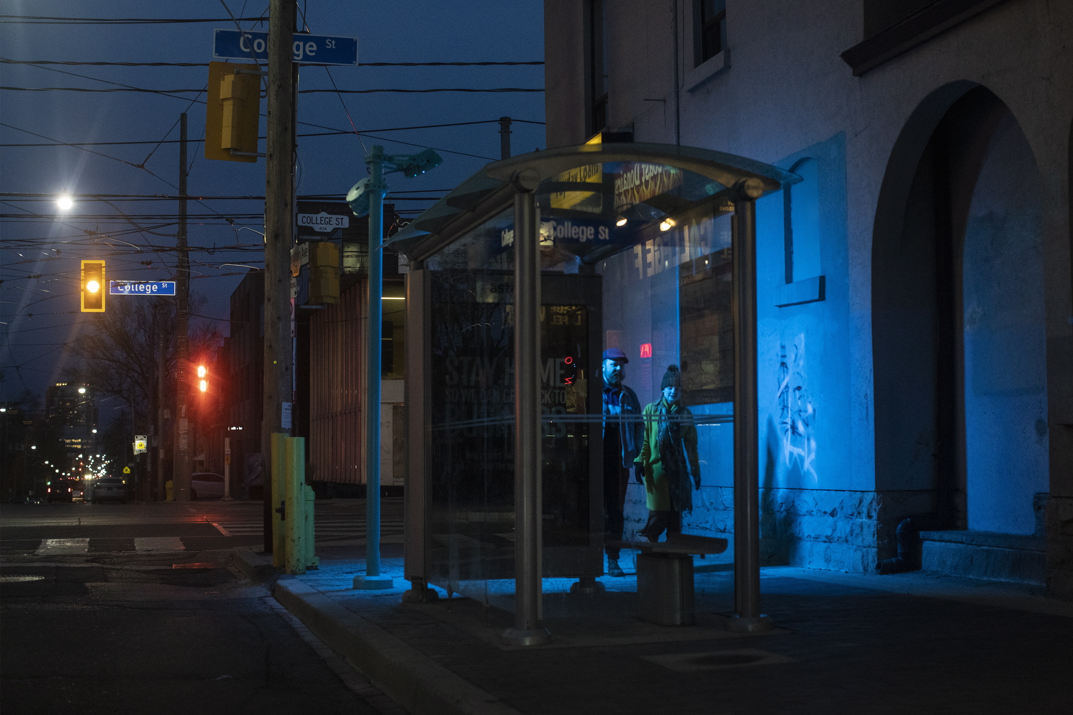 People walk at night in Toronto