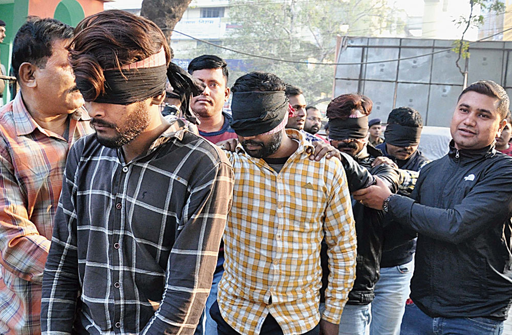 Police with the killers of high court lawyer Jitendra Kumar in Patna on Saturday, December 8, 2018.
