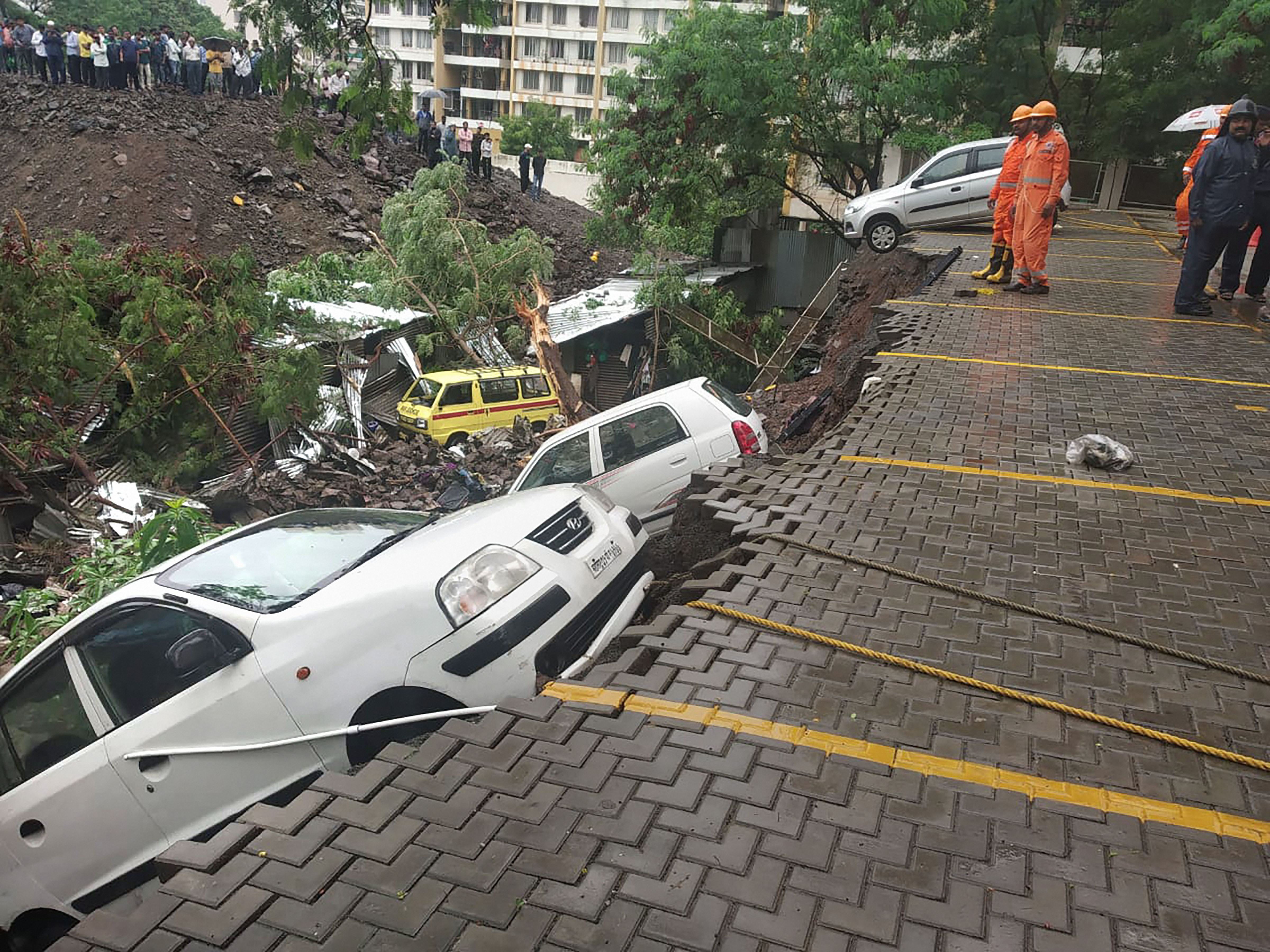 A dislodged car at the site where a portion of the compound wall of a housing society collapsed on shanties adjacent to it in the Kondhwa area in Pune on June 29.