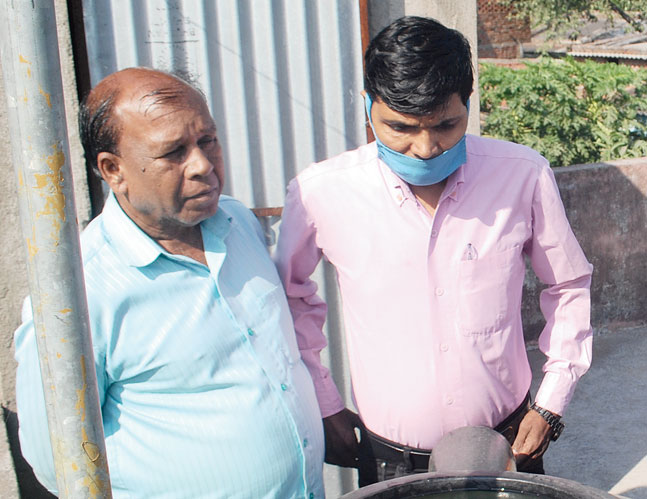 Health department officials inspect an open water tank in Chalchalia Dhaura, Jharia, Dhanbad, on Wednesday.