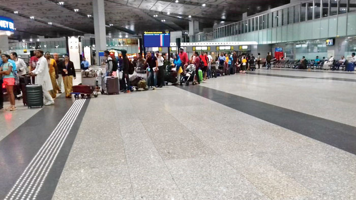 Passengers stand in a long queue at the city airport