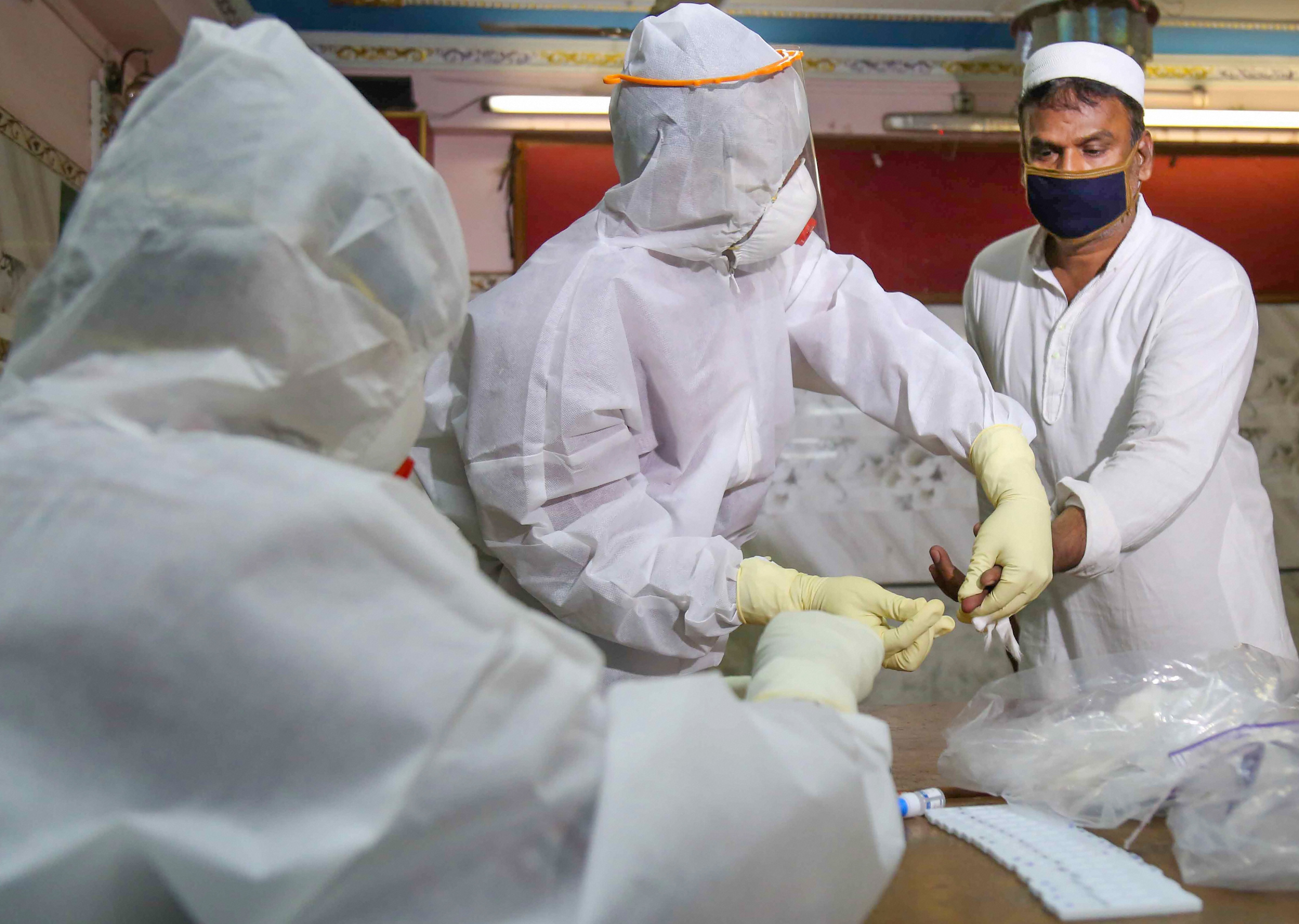 Health workers conduct a COVID-19 test of a person in wake of the coronavirus pandemic, during the nationwide lockdown