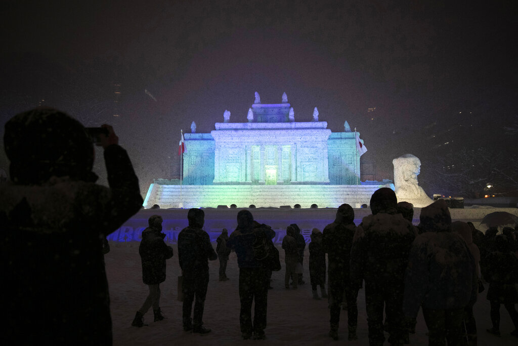 Tourists gather in front of a large snow sculpture of Poland's Palace on the Isle during the annual Sapporo Snow Festival at Odori Park in Sapporo
