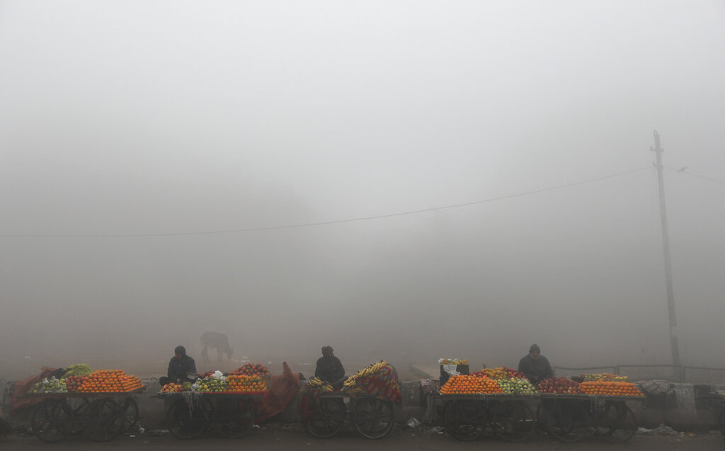 Fruit sellers wait for customers amidst early morning fog in New Delhi, Monday, December 30, 2019.