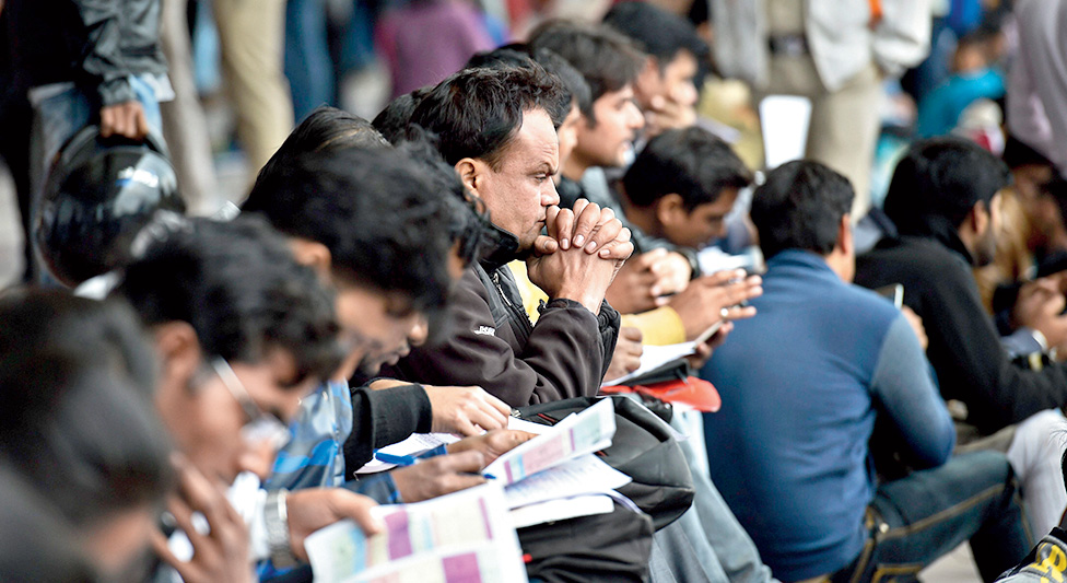 A man looks on as others fill forms during the two-day Mega Job Fair, at Thyagaraj Stadium in New Delhi on Monday, January 21, 2019.
