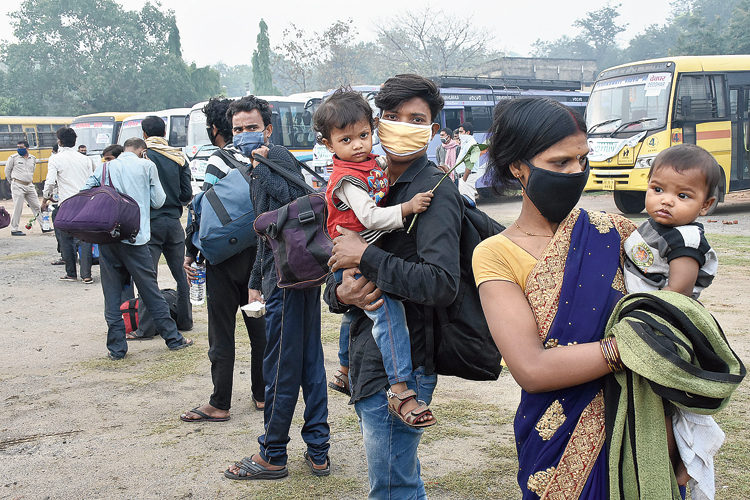 Migrant labourers of Jharkhand stand in queue at Golf Ground in Dhanbad after arriving from Surat in Gujarat.