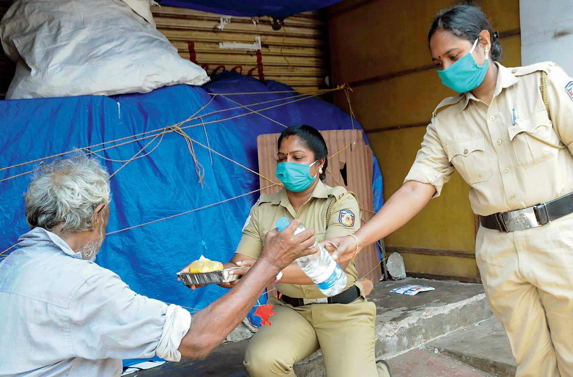 Police personnel hand over food during the lockdown in Kozhikode, Kerala, on Sunday.
