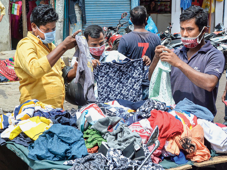 Customers at a roadside shop that was reopened after restrictions were eased in Guwahati on Monday.
