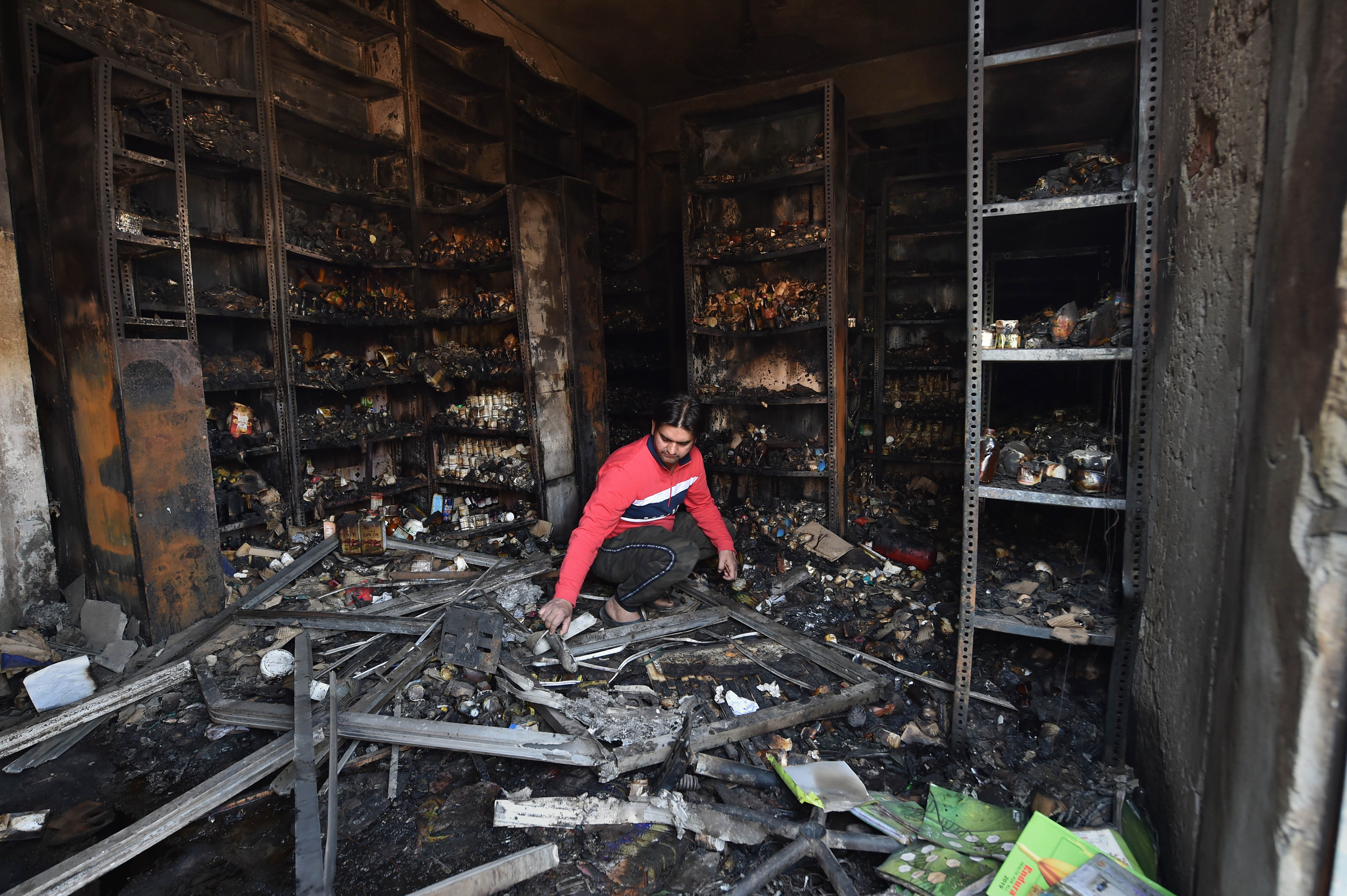 A shopkeeper sorts through the charred remains of a vandalized and burned shop, following the riots, at Khajuri Khas extension area of northeast Delhi, Friday, February 28, 2020. There were some areas of normalcy in the riot-hit localities of northeast Delhi with shops opening.