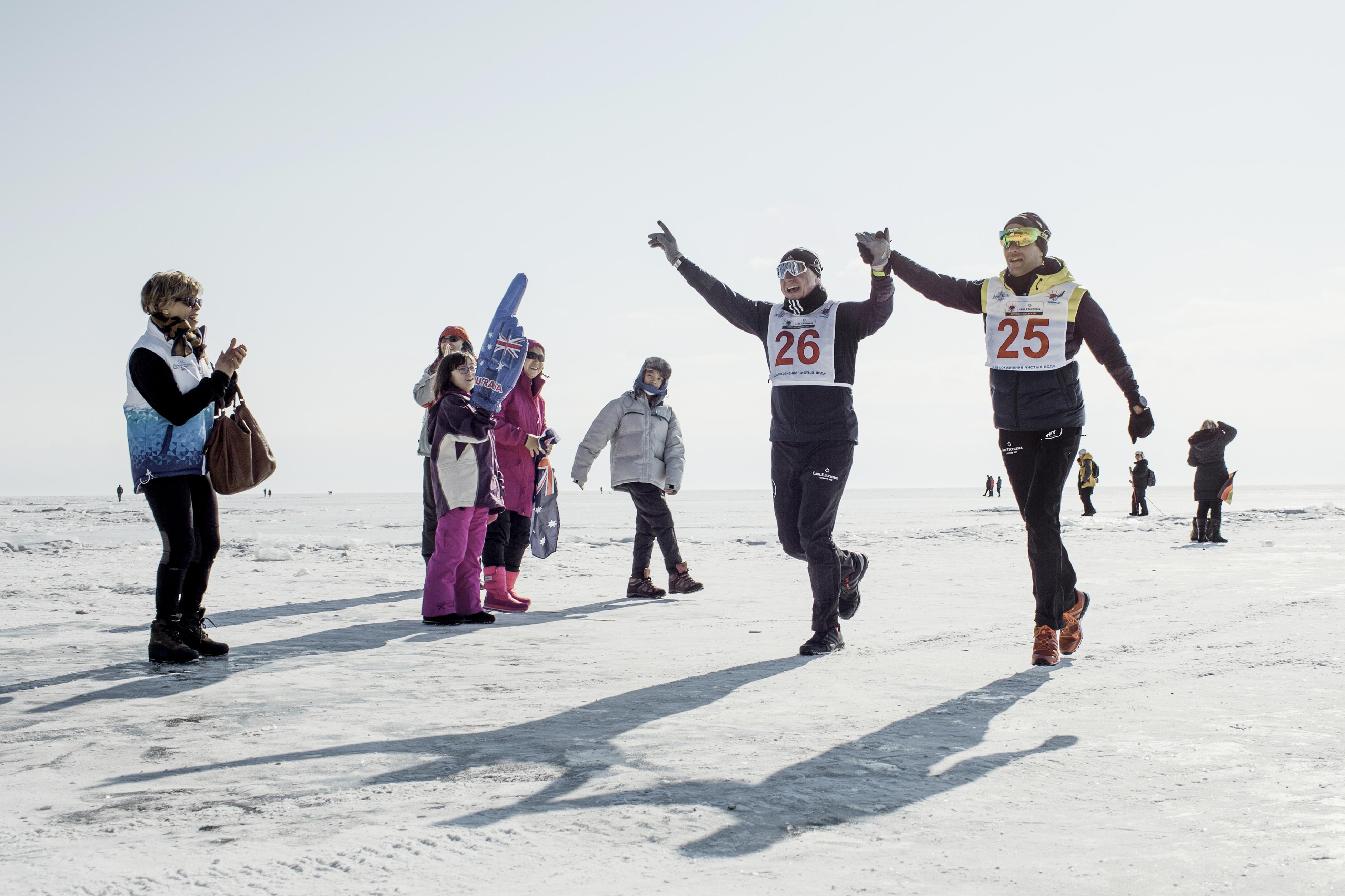 Running partners Vladimir Voloshin (left) and Laurent Lecamp at the finish line of the Baikal ice marathon.