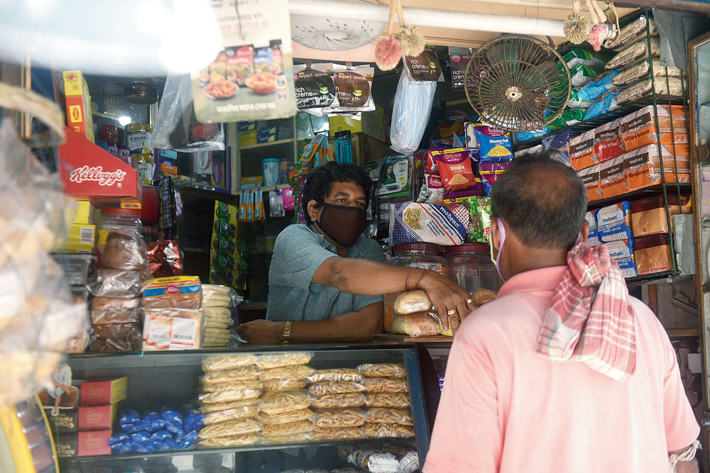 Biswajit Saha, the owner of Laxmi Narayan Stores on Hindusthan Road, talks to a customer.