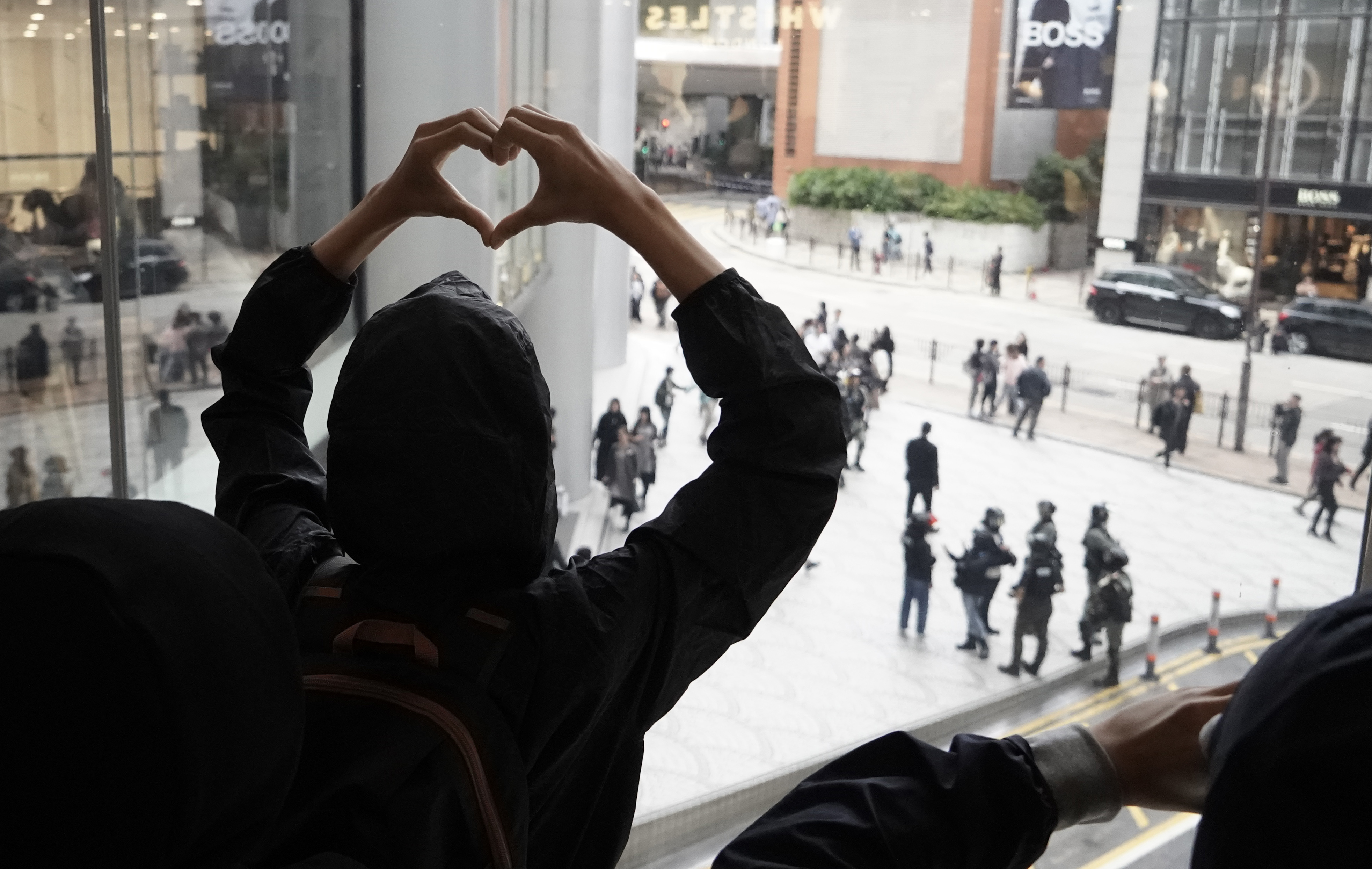 Hong Kong pro-democracy protesters show a heart sign to riot police in downstair as protesters march in Harbour City shopping mall in Hong Kong, on December 21, 2019