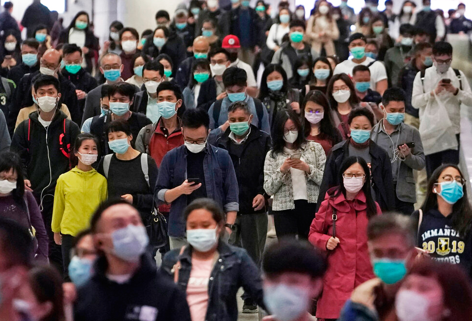 People wearing masks as a precaution against the COVID-19 illness walk inside a subway station during rush hour in Hong Kong, Wednesday, March 11, 2020.