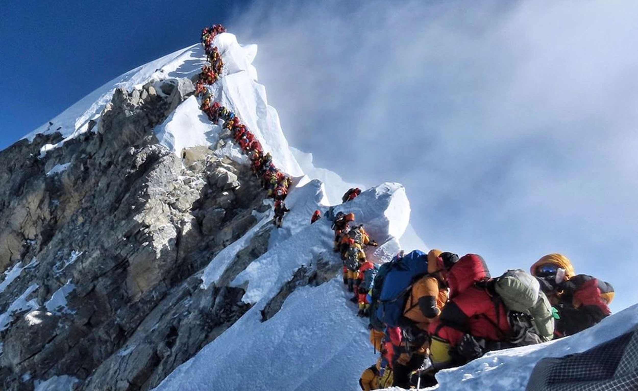 In this May 22, 2019, photo, a long queue of mountaineers line a path on Mount Everest