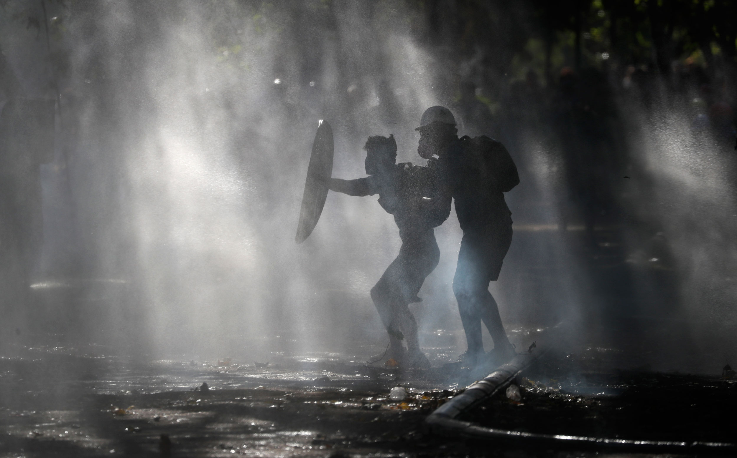 Anti-government demonstrators shield themselves from water cannons in Santiago, Chile, on Friday.