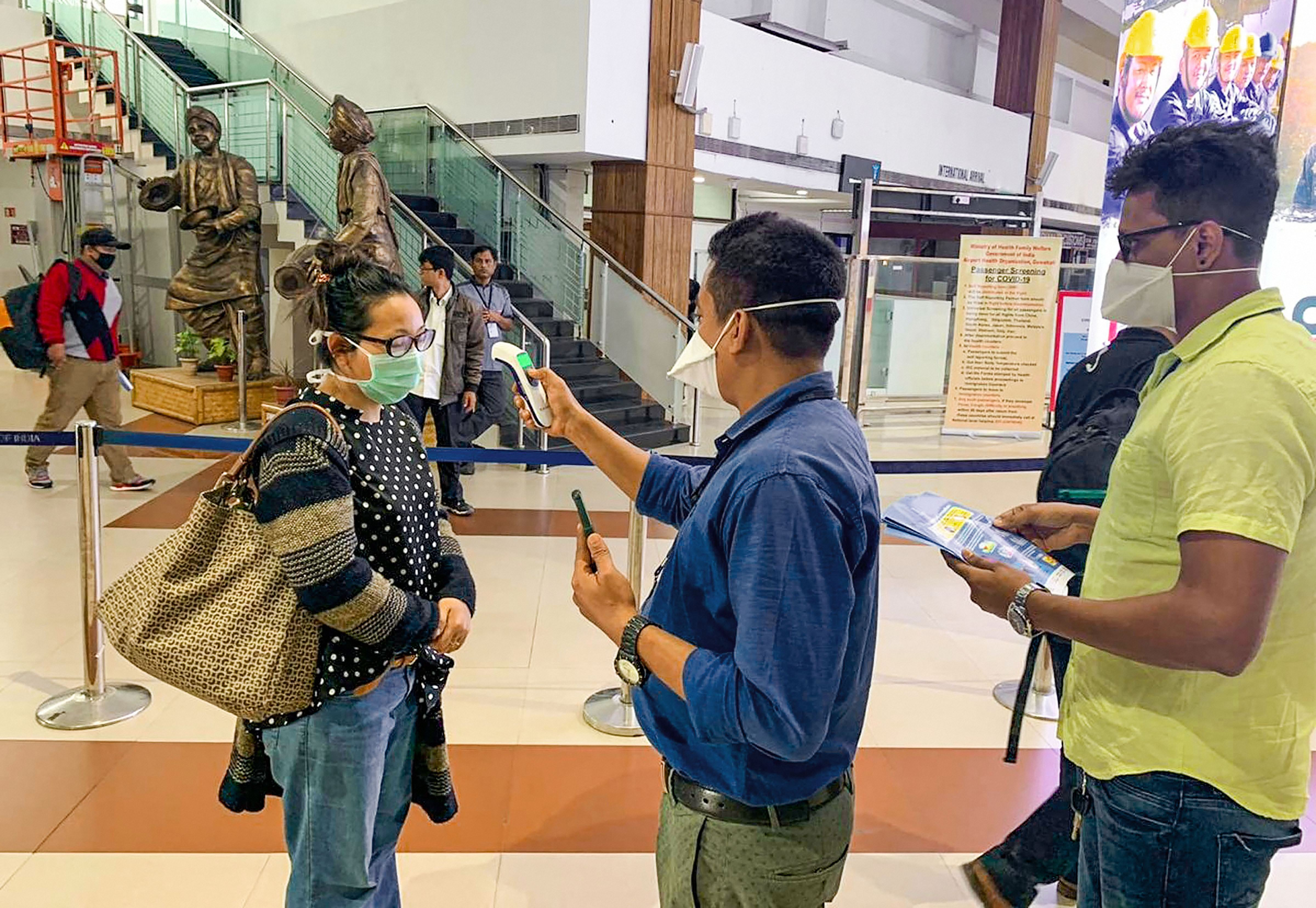 Passengers undergo a thermal screening test in the wake of novel coronavirus scare at Lokpriya Gopinath Bordoloi International Airport in Guwahati, Monday, March 9, 2020