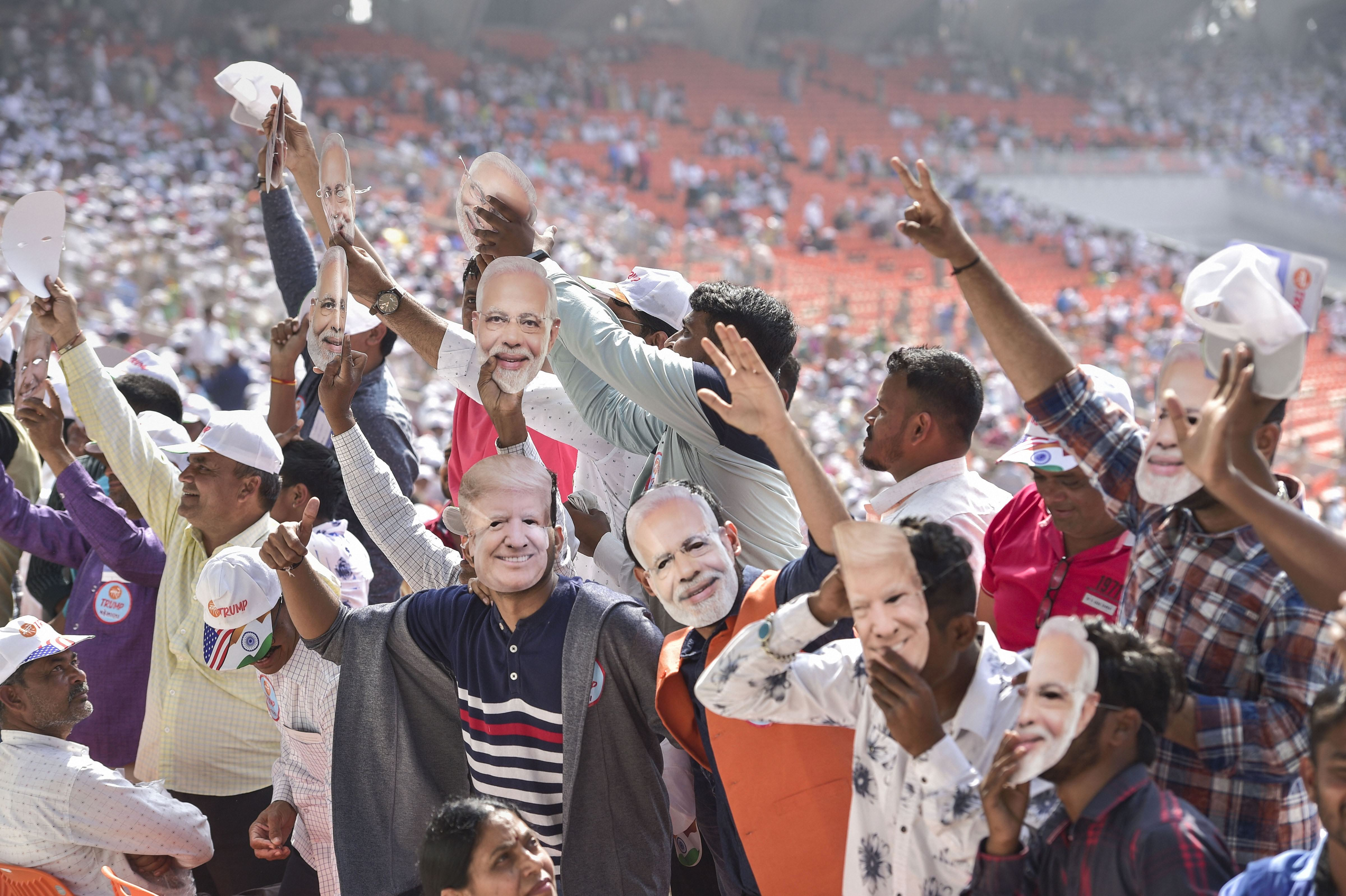 People wearing Prime Minister Narendra Modi's and US President Donald Trump's masks wave as they arrive to attend the 'Namaste Trump' event at Sardar Patel Motera Stadium, in Ahmedabad, Monday, February 24, 2020