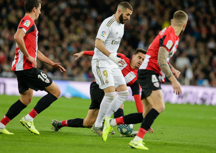 Real Madrid's Karim Benzema, (center) controls the ball between Athletic Bilbao's players during a Spanish La Liga football match between Real Madrid and Athletic Bilbao at the Santiago Bernabeu stadium on Sunday