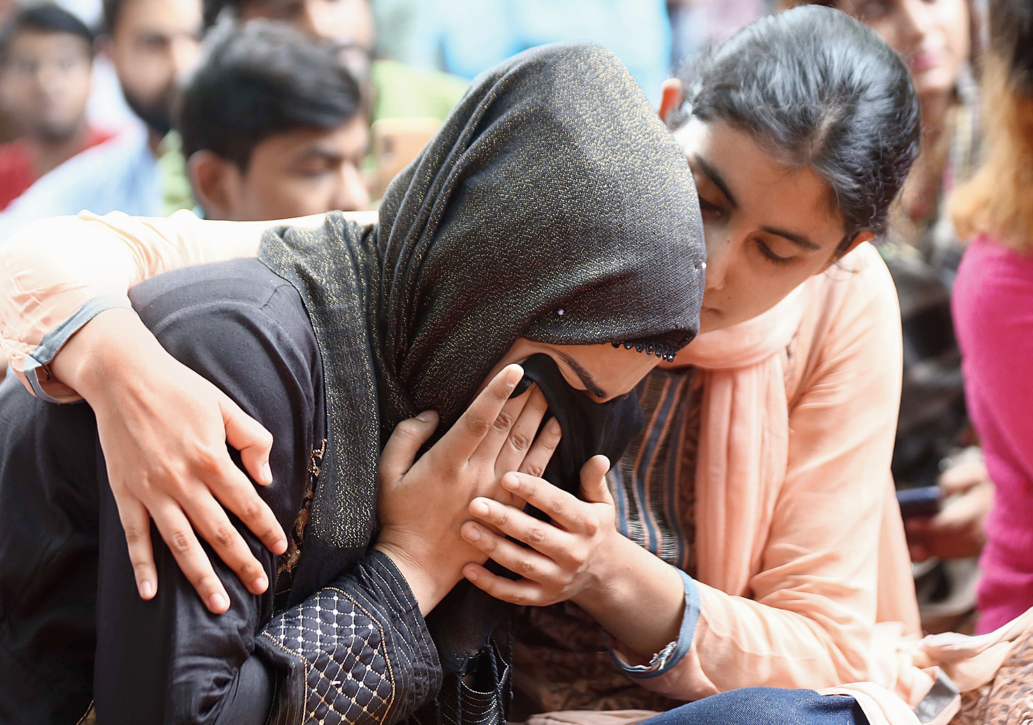 A girl breaks down as Zubair Rashid recites the poem at the event on Jantar Mantar Road in New Delhi on Monday.