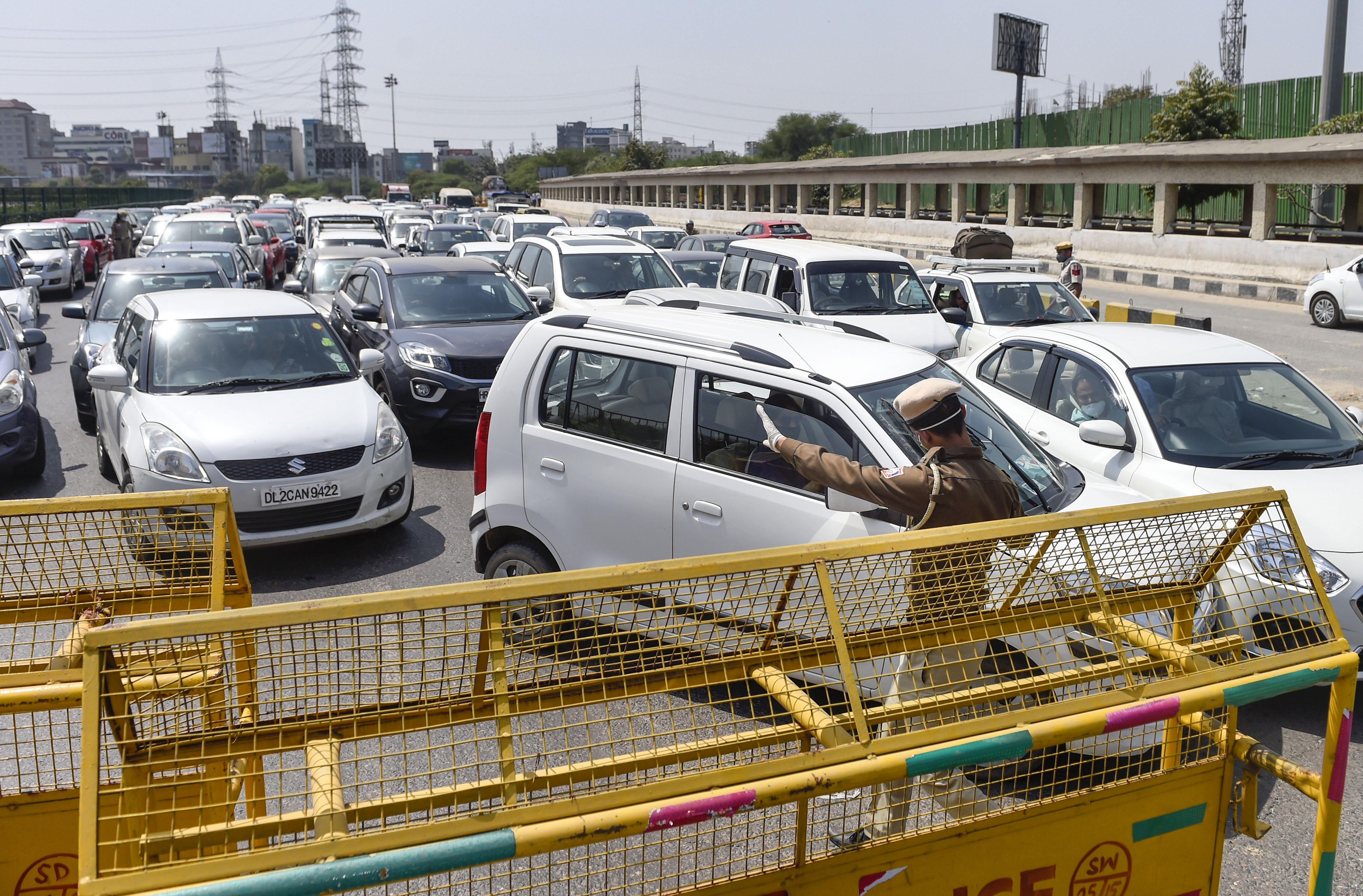 A police official checks ID cards of commuters on the Gurgaon-Delhi border after lockdown in New Delhi on Monday.