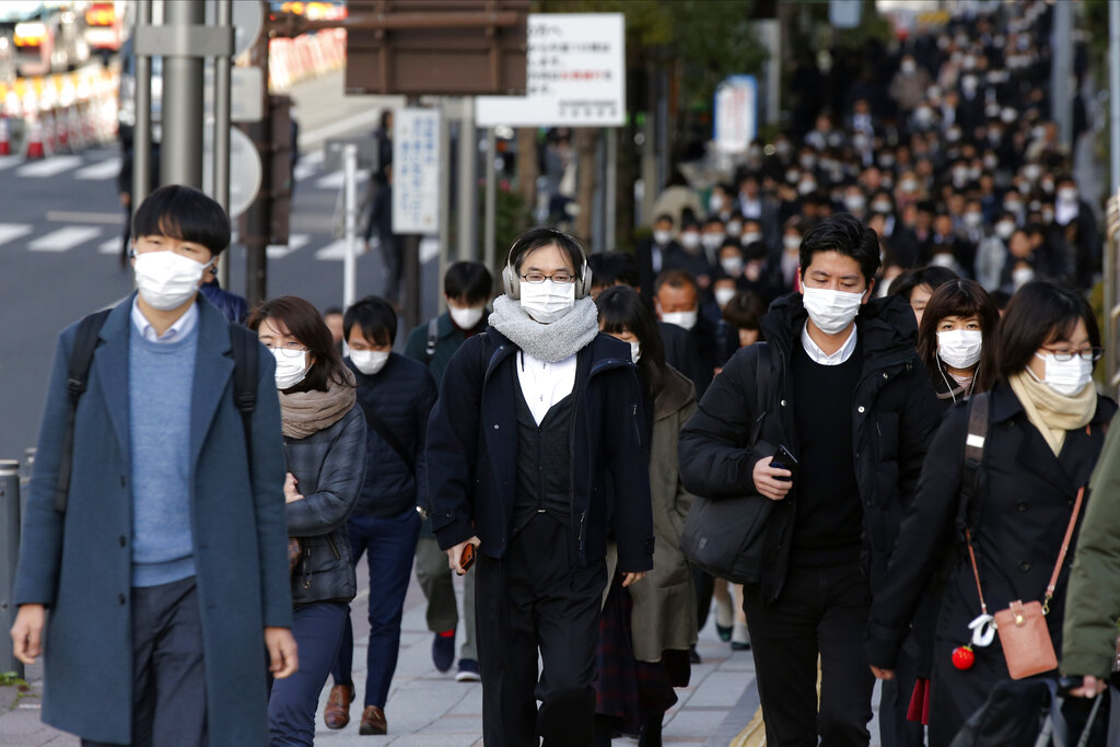 People wear masks as they commute during the morning rush hour, in Chuo district in Tokyo