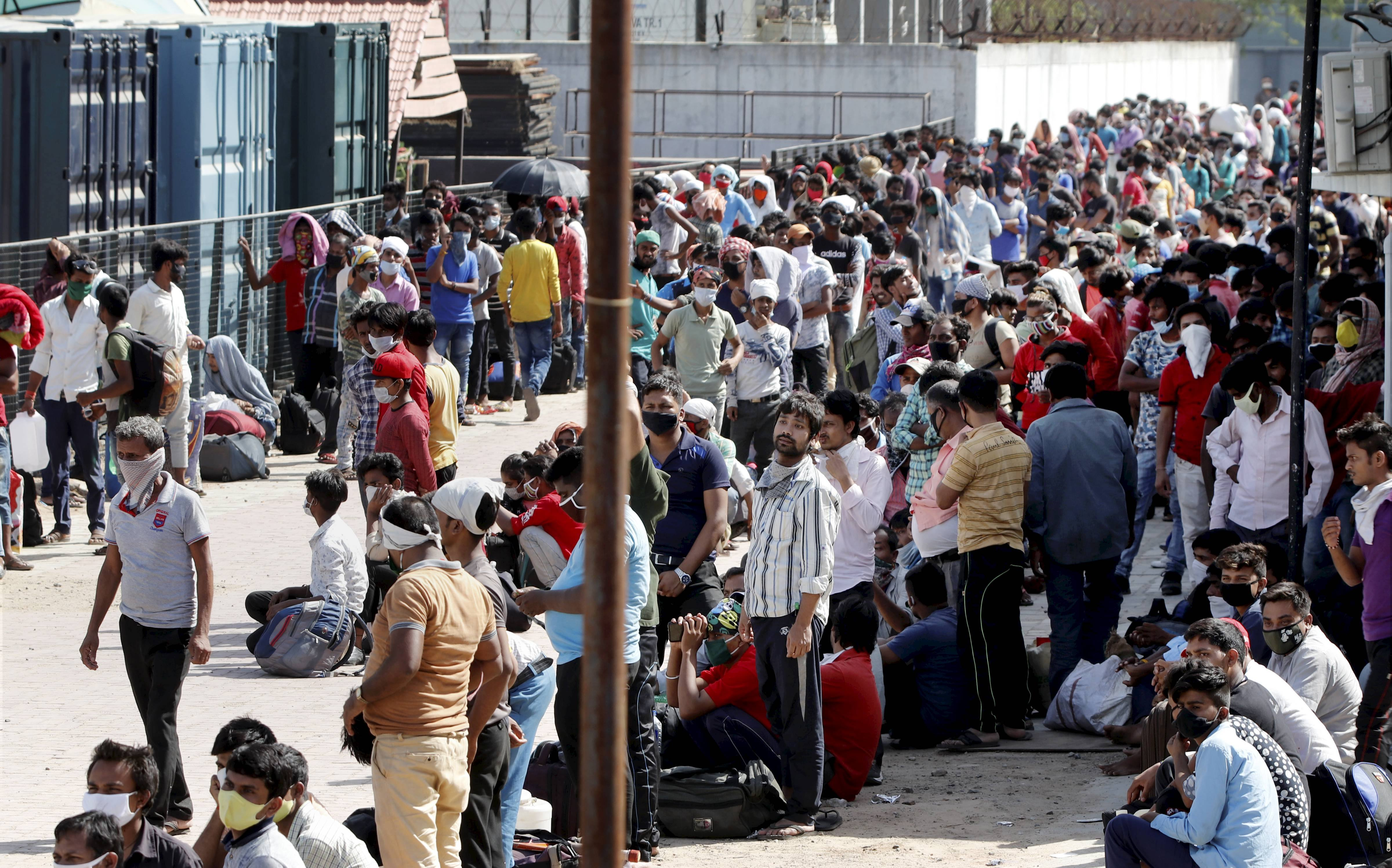 Migrant workers and their families wait in Ahmedabad on Friday for transport to the railway station to return home
