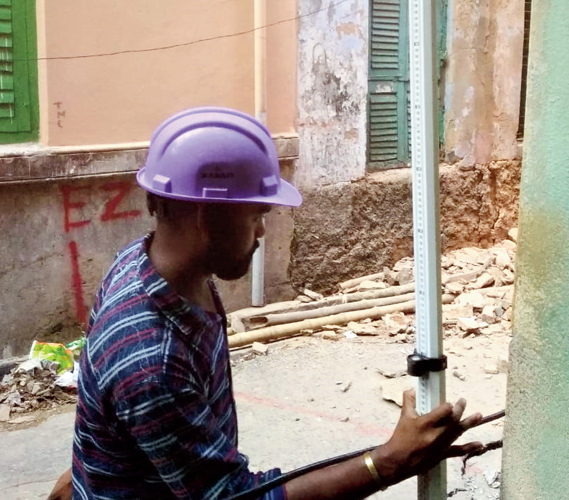 An engineer places a scale to measure subsidence suffered by the building.