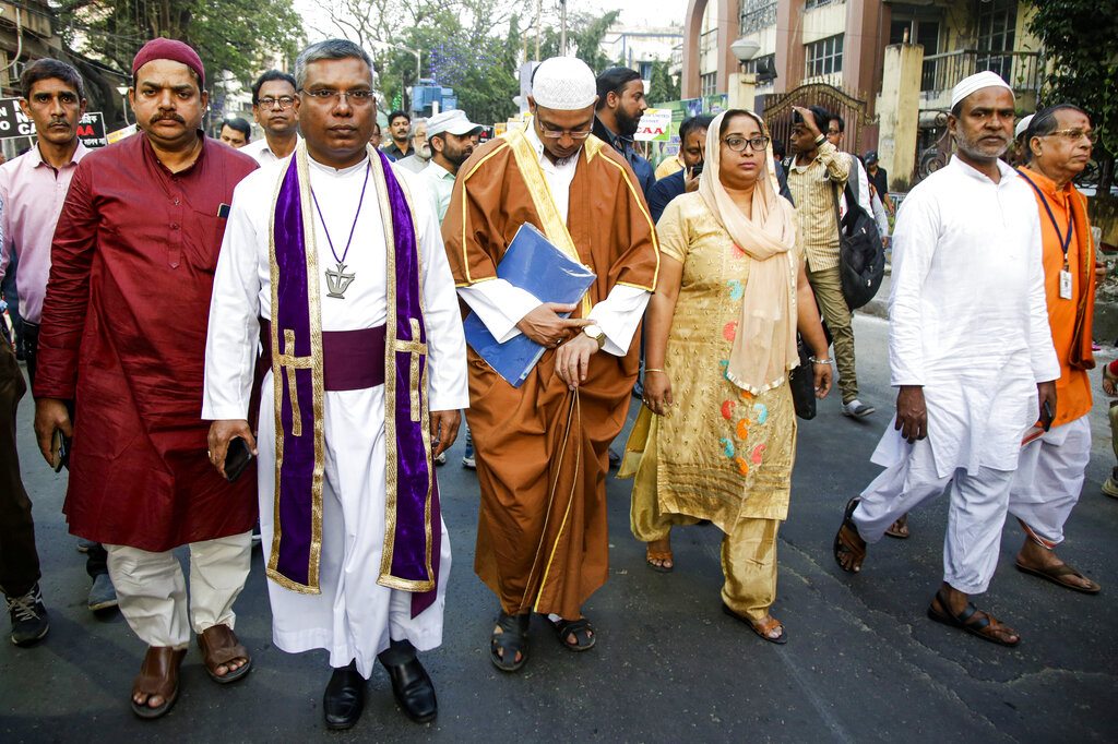 Priests of different communities participate in a procession during a mass marriage ceremony for more than eighty couples of various religions in Kolkata, on Friday