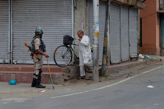 In this Tuesday, Aug. 6, 2019 photo, a Kashmiri man carries his cycle and crosses a temporary check point, with a paramilitary soldier standing beside it during curfew in Srinagar, on Wednesday, August 7, 2019.