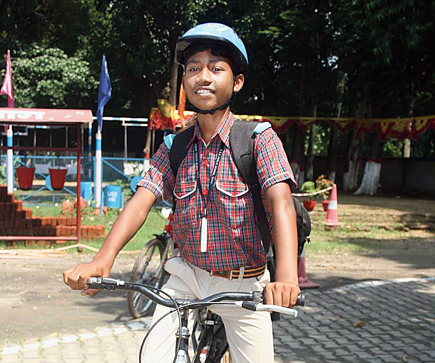 Sagar Marandi rides to school with helmet on in Dhanbad on Monday.