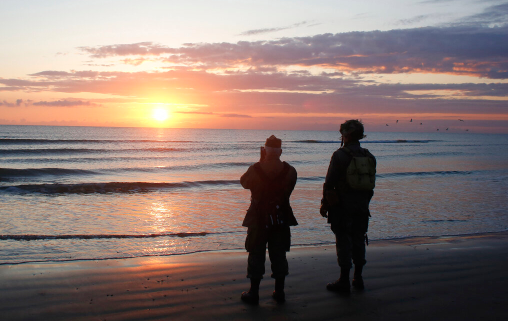 World War II re-enactors stand looking out to sea on Omaha Beach, in Normandy, France, at dawn on Thursday, June 6, 2019 during commemorations of the 75th anniversary of D-Day.
