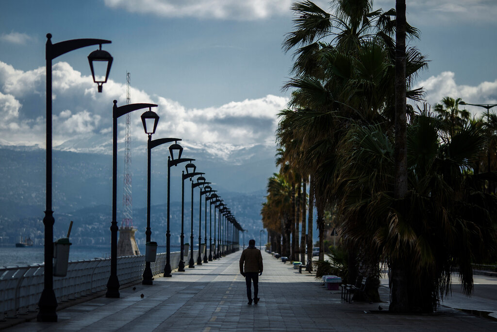 A man walks at Beirut's seaside corniche, or waterfront promenade, along the Mediterranean Sea, which is almost empty of residents and tourists in Beirut, Lebanon, Saturday, March 21, 2020.