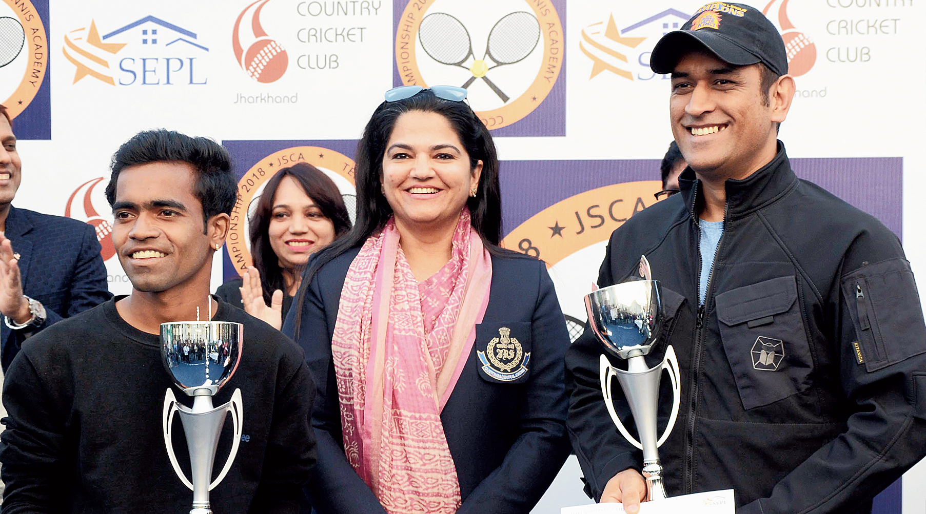 Mahendra Singh Dhoni receives a trophy from income tax commissioner Monika Batra at a tennis tourney at JSCA stadium in Ranchi on Friday.