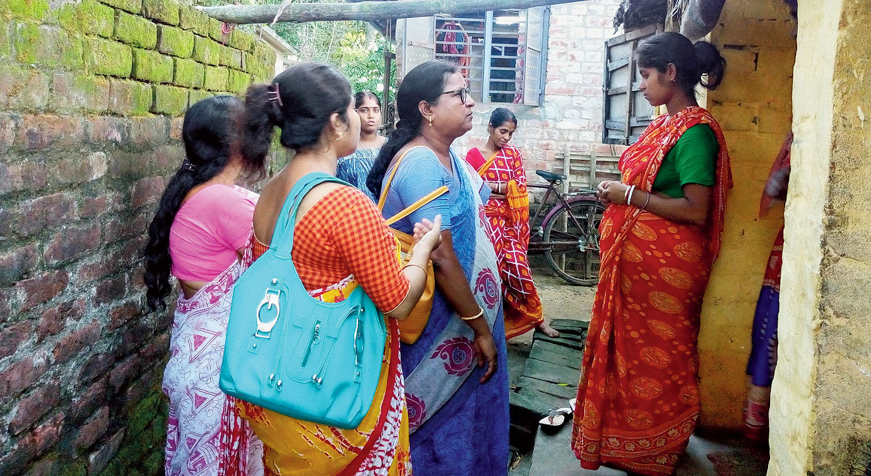 ICDS workers speak to Moumita Sandhukhan (right) at her home in Santipur on Sunday.