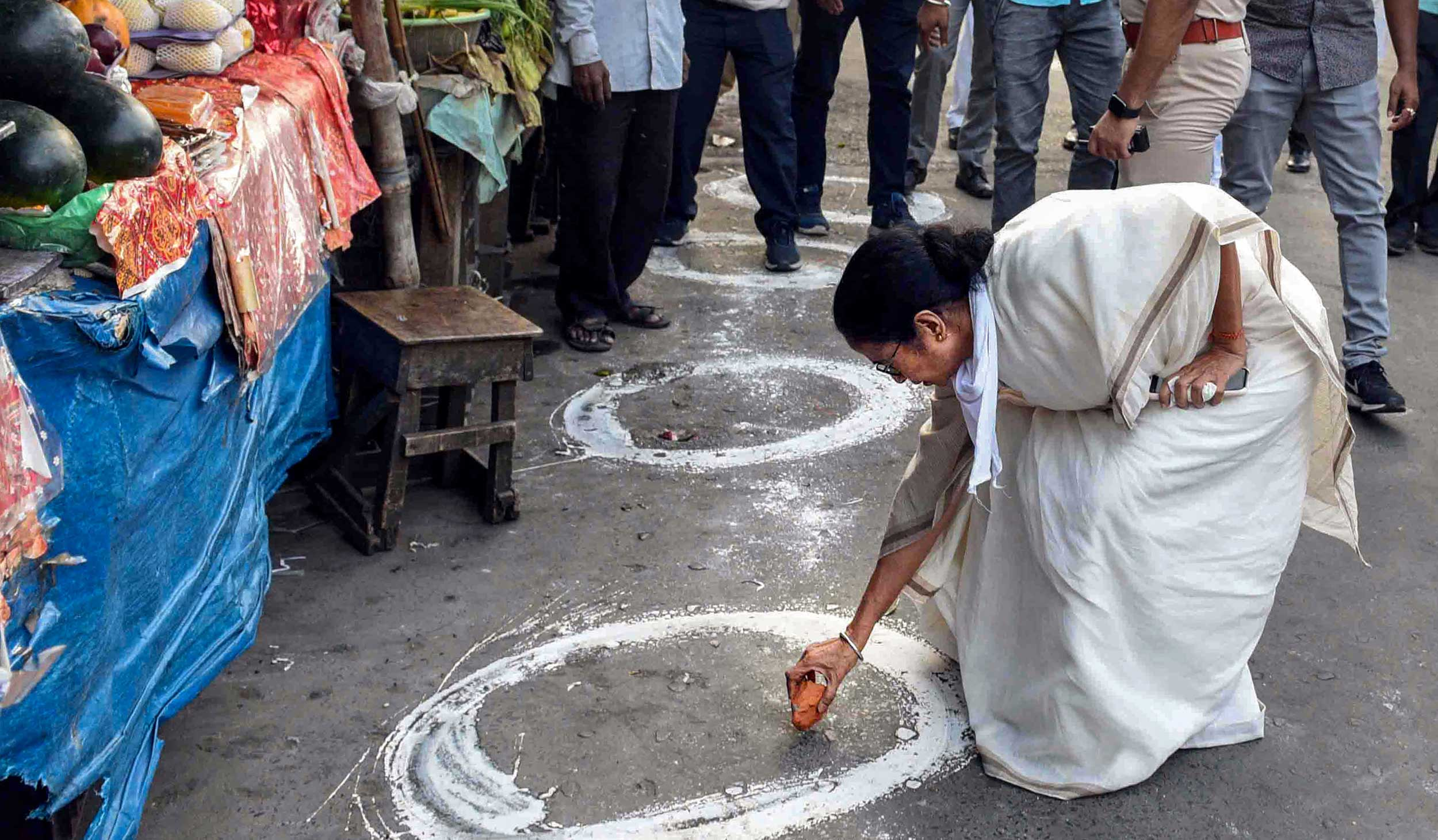 With a broken brick, Mamata draws a social-distancing circle for shoppers at a market in Calcutta on Thursday.