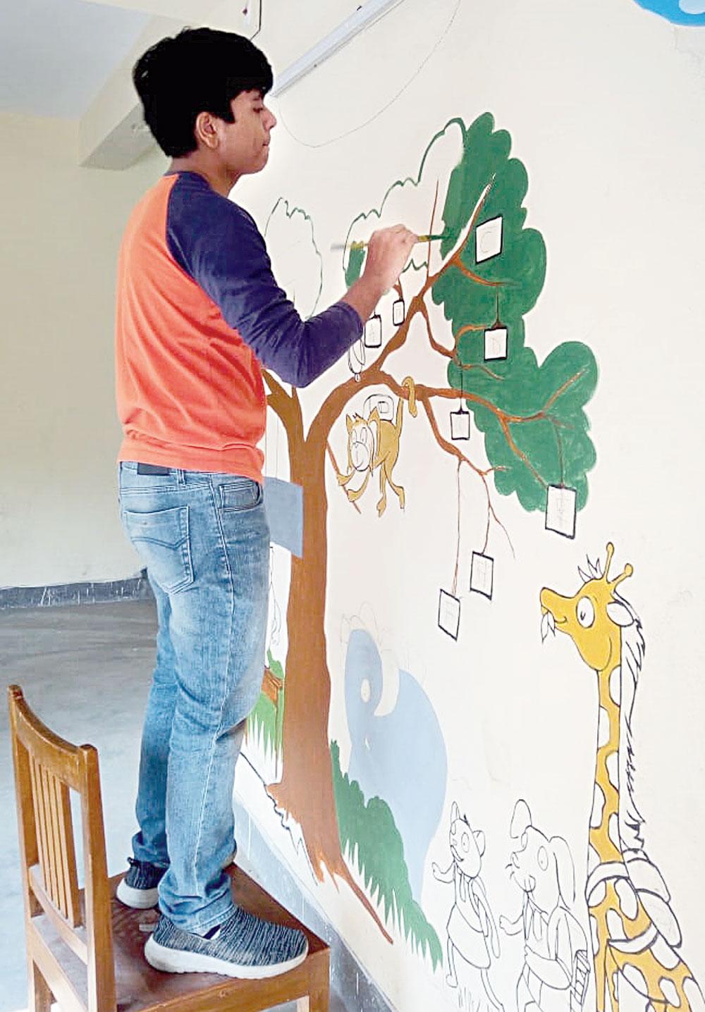 Harshit Jain paints a wall of Nandipur Swami Vivekananda Vidyamandir, a school in Dum Dum Park run by a fish seller