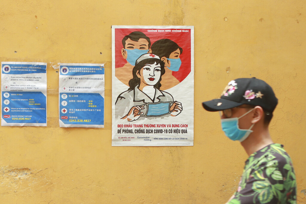 A masked man walks past a poster encouraging people to wear face masks correctly in Hanoi, Vietnam, Thursday, Apr. 23, 2020. Business activities resume in Vietnam as the country lifts the nationwide lockdown to contain the spread of Covid-19.
