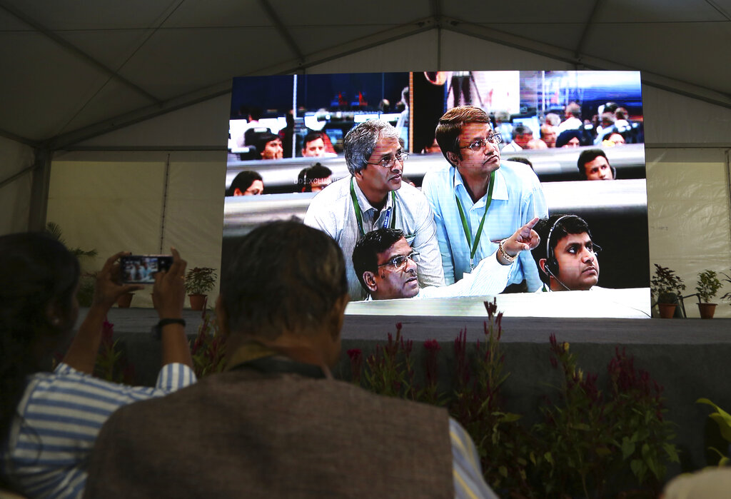Live pictures of Isro scientists reacting are displayed on a big screen at their Telemetry, Tracking and Command Network facility in Bangalore. Isro says it has lost communication with its unmanned spacecraft's lander and rover.