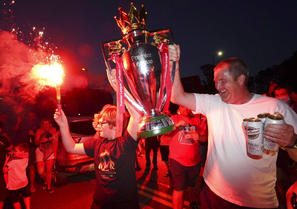 Liverpool supporters hold a replica Premier League trophy as they celebrate outside of Anfield Stadium in Liverpool, England on Thursday.