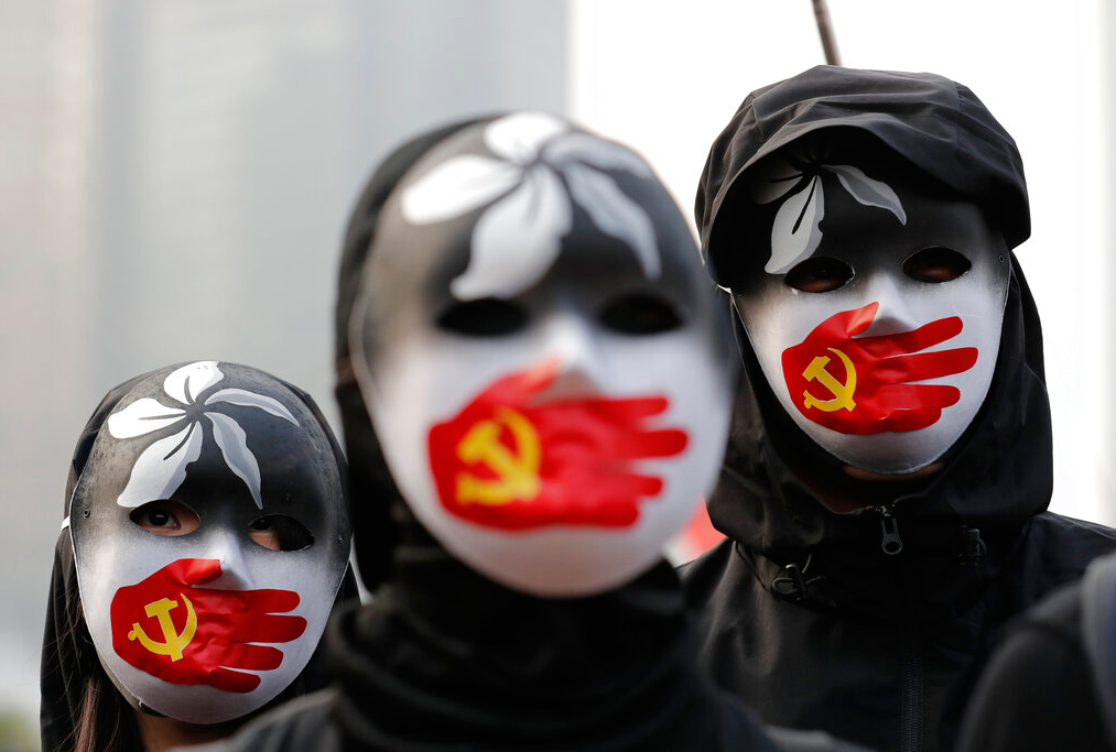 People wearing masks stand during a rally to show support for Uighurs and their fight for human rights in Hong Kong, Sunday, December 22, 2019.