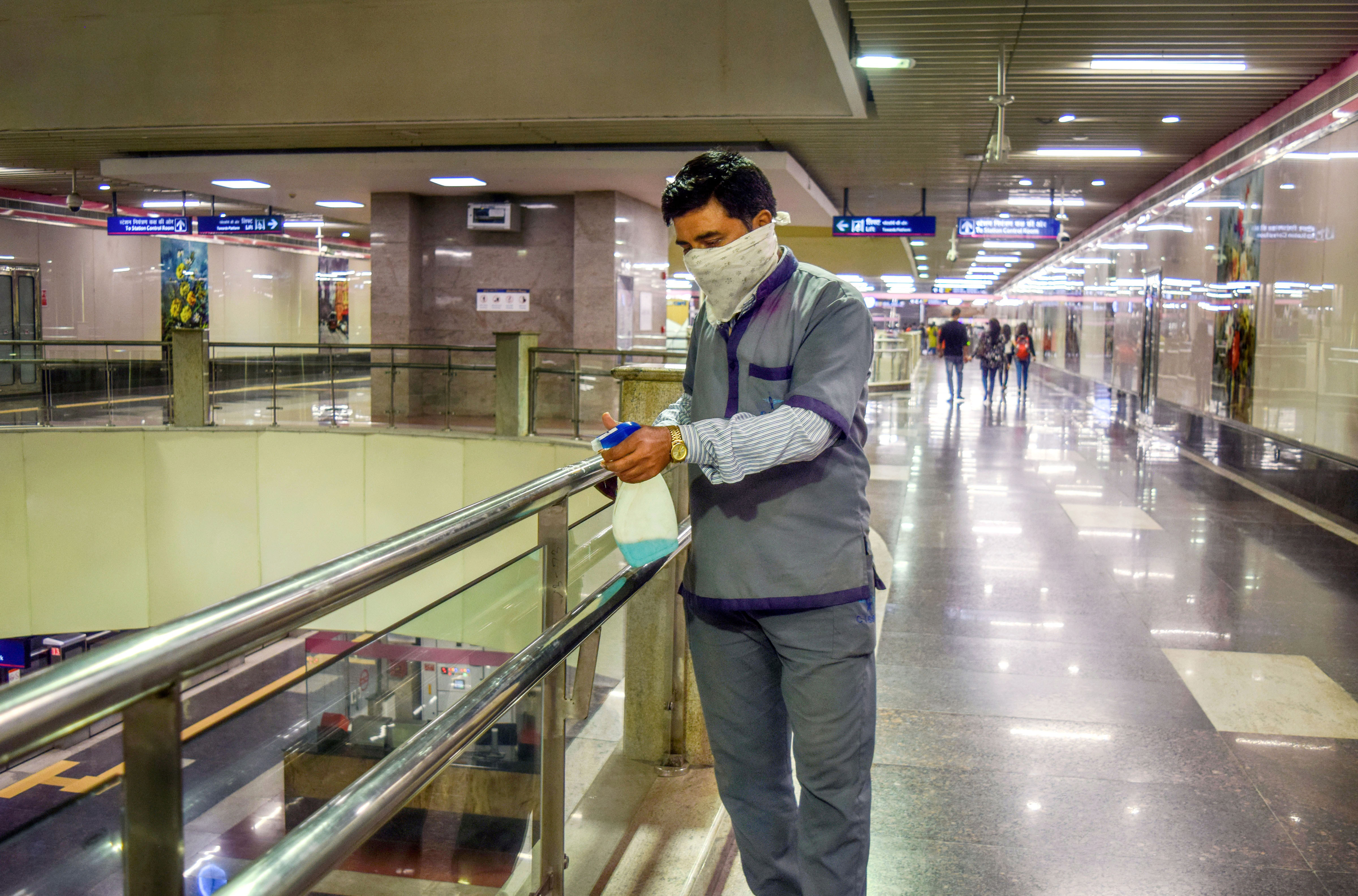 A worker cleans hand railings at pink line metro station to prevent the spread of coronavirus, in New Delhi, Sunday, March 15, 2020