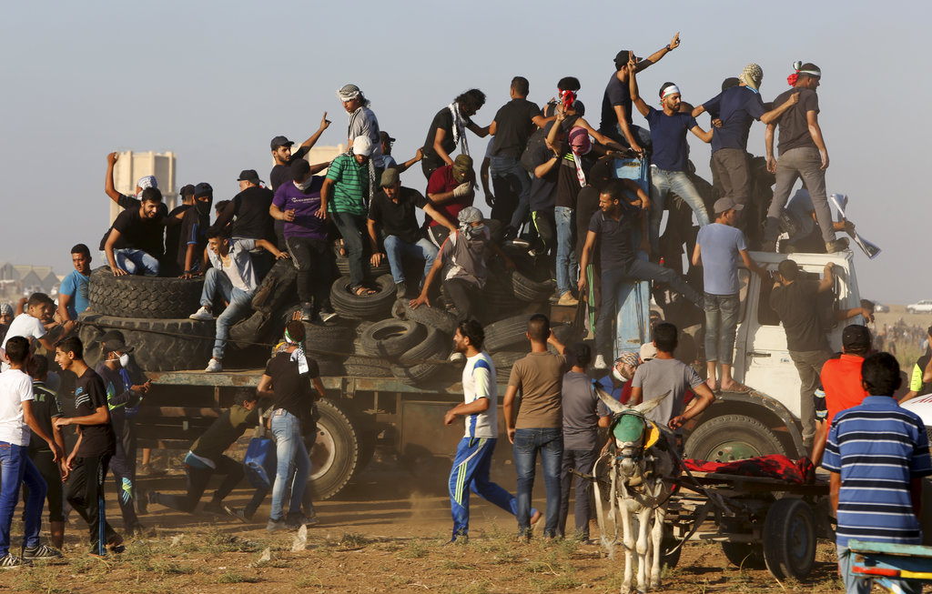 In this September 21, 2018, file photo, protesters arrive on a truck with tyres to burn near the the fence of the Gaza Strip border with Israel during a protest.