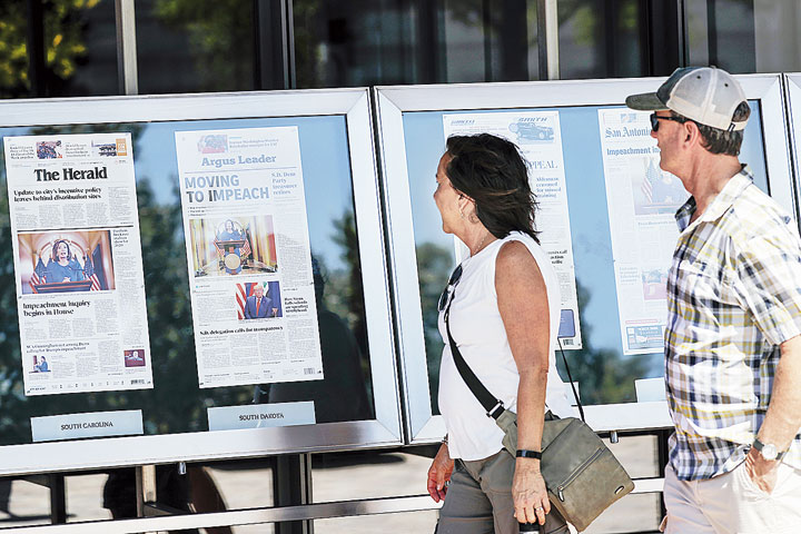 Visitors read newspaper front pages on display at the Newseum in Washington on September 25