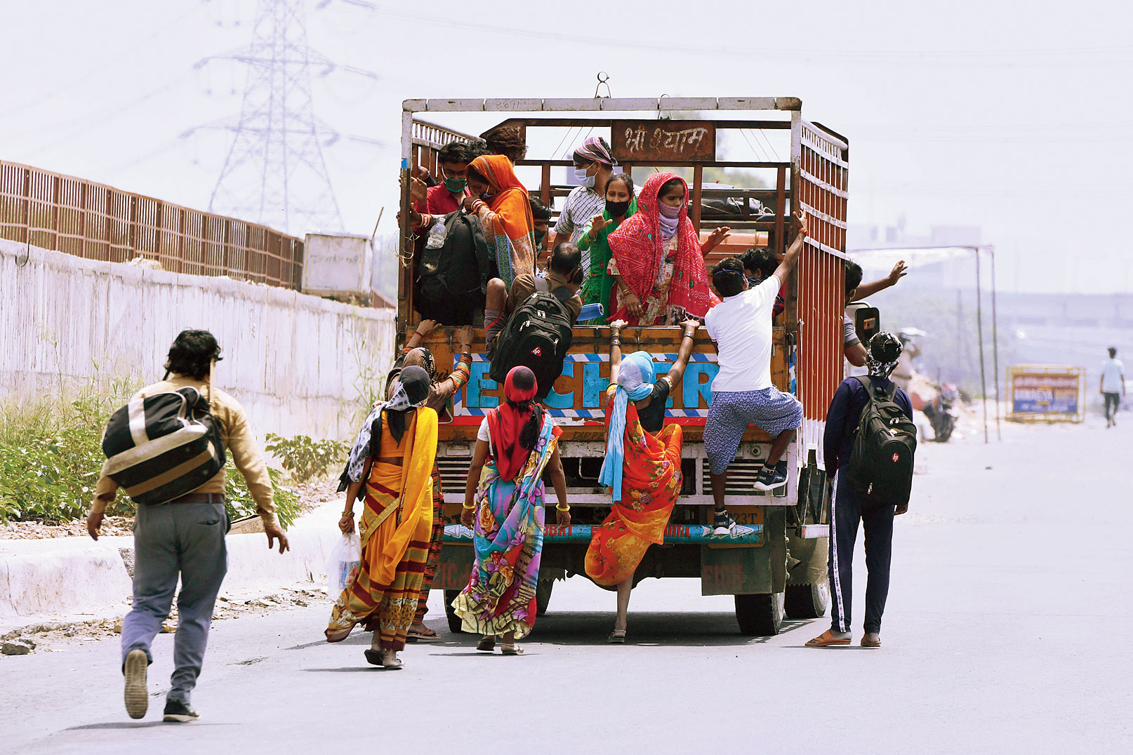 Migrants headed to their home state board a truck in Ghaziabad on Thursday.