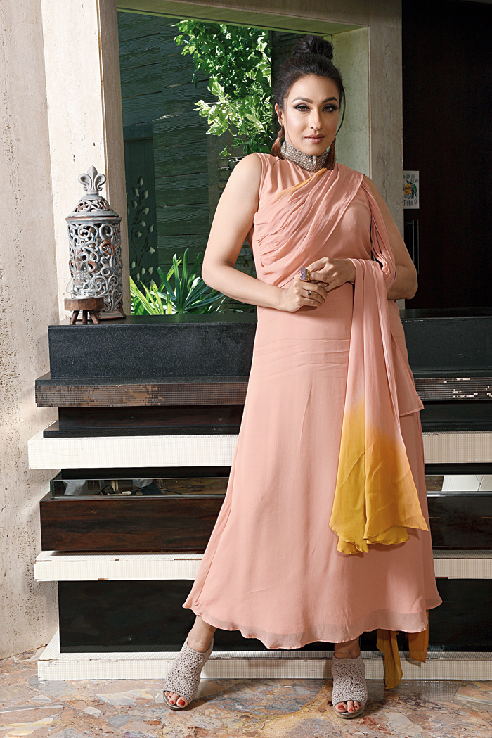 "Rituparna slipped into this sleeveless, peach georgette number with an embellished neckline and a touch of ombre. A top knot and peachy lips completed the look that the actress described as ""smart yet elegant""."