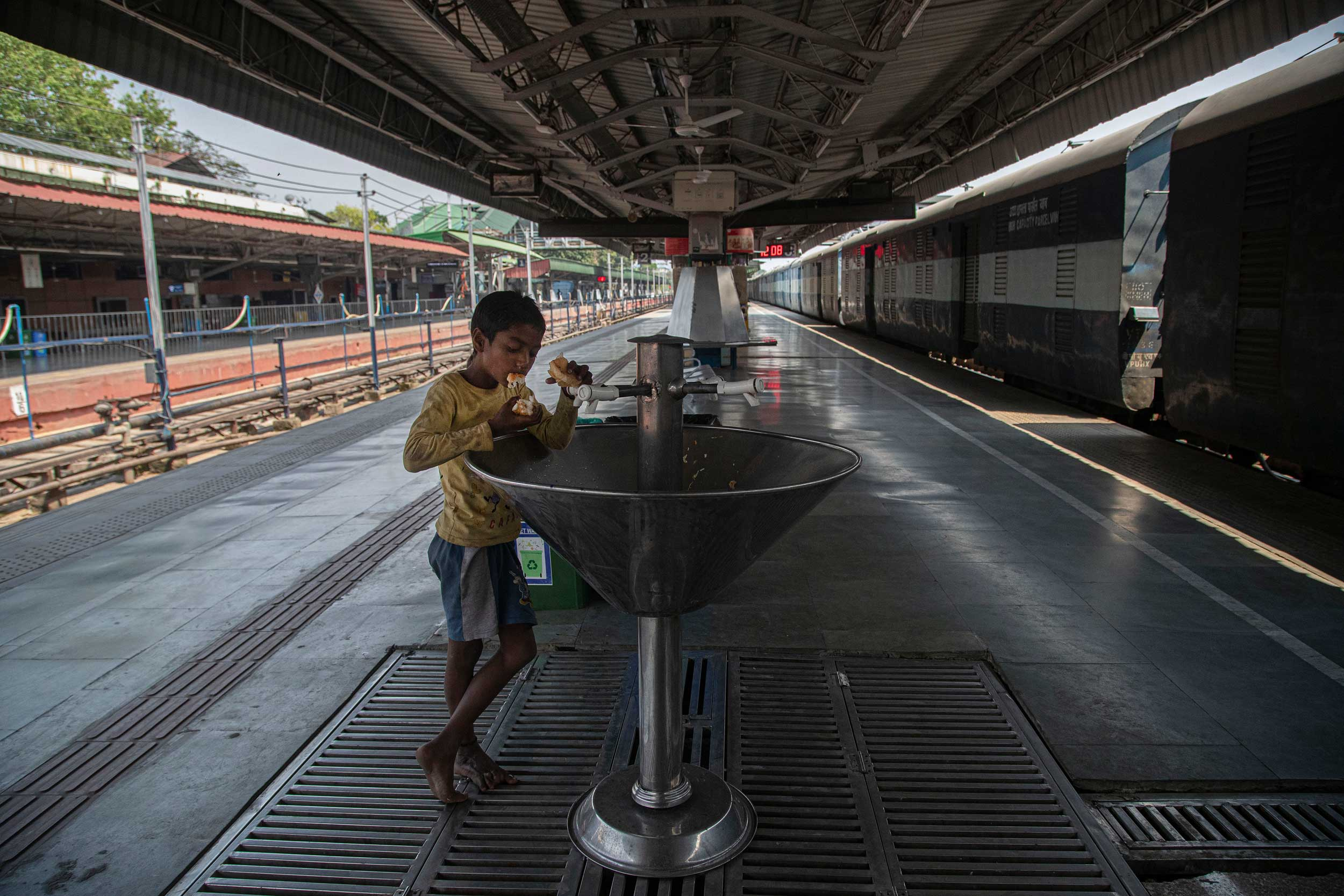 A homeless boy eats bread from a garbage bin at an empty railway station during the lockdown in Guwahati on Wednesday.