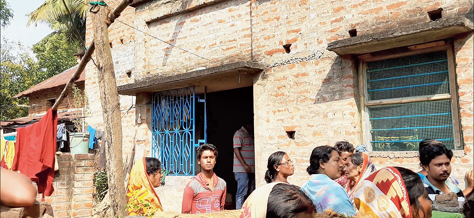 Villagers assemble in front of the house of the youth who committed suicide.