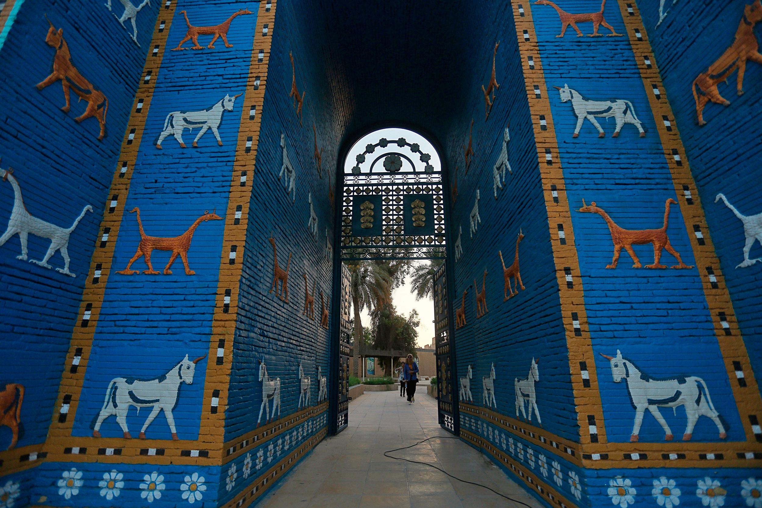 People walk near the Ishtar Gate in the ancient city of Babylon near Hilla, Iraq, on July 5, 2019.