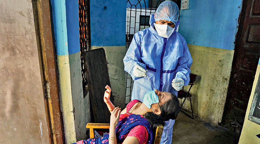 A health worker collects a sample from a person for Covid-19 test in Thane on Friday.