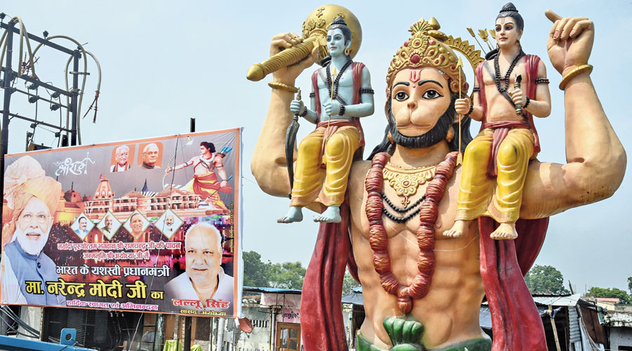A hoarding showing Narendra Modi and others beside a statue of Hanuman on Thursday, ahead of the foundation-laying ceremony for the Ram temple in Ayodhya.